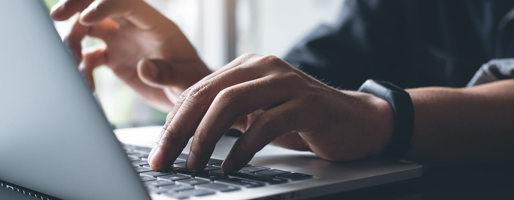 lifestyle image of hands typing on a laptop