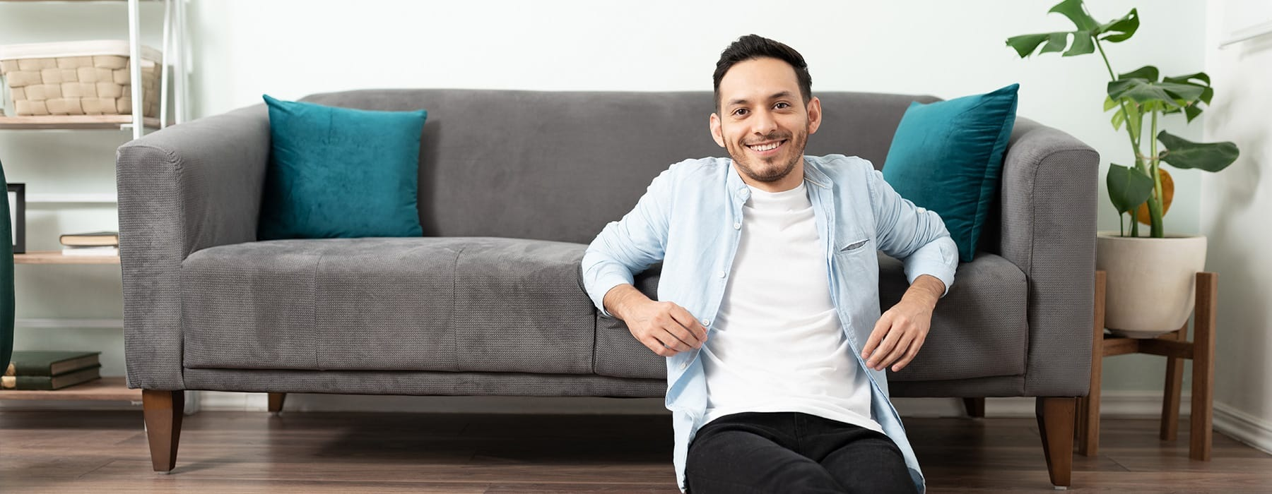lifestyle image of a man sitting on the floor, beside a modern couch